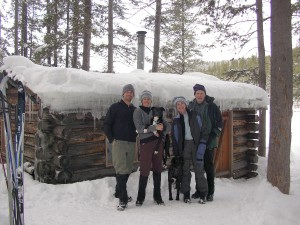 family in front of cabin