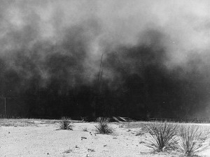 Black and white photograph of billowing black clouds of dust scoured landscape.